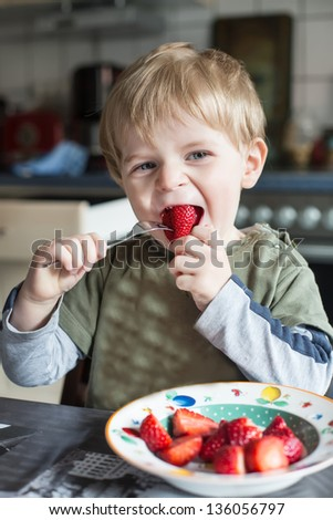 Little boy eating fresh strawberries in the kitchen