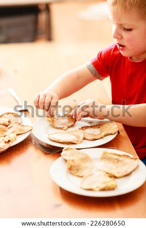 Little boy eating fried apple in pancake dough or apple fritters pancakes with icing sugar at home - stock photo
