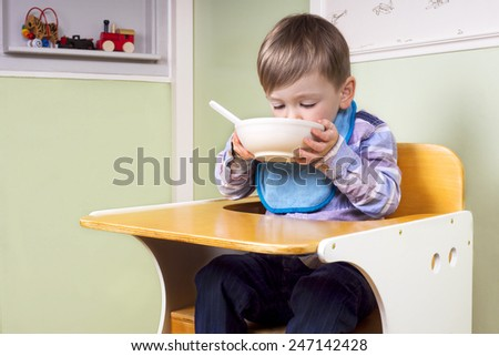 little boy eating lunch in his chair - stock photo