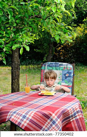 little boy eating outdoors - French fries with ketchup - stock photo