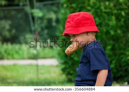 little boy eating outdoors (Shallow DOF). - stock photo