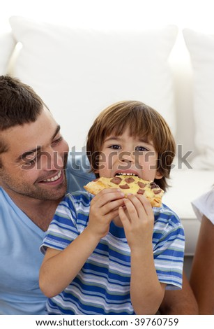 Little boy eating pizza in living-room with his father - stock photo