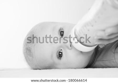 little boy eats from a bottle - stock photo