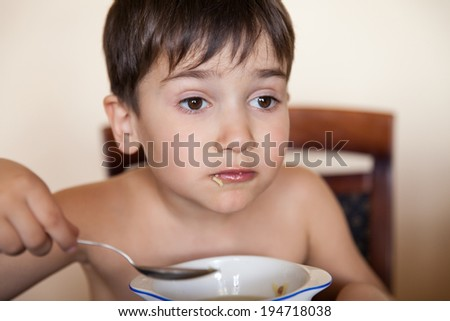 Little boy eats with a spoon from a plate - stock photo