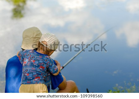 Little boy embracing and fishing with father in blue sky reflection - stock photo