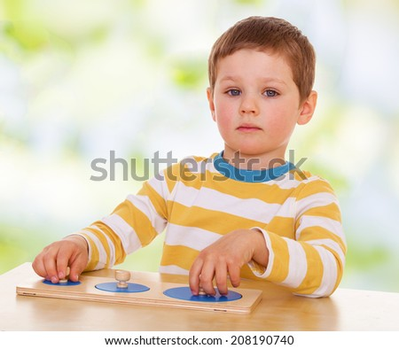 little boy engaged in Montessori kindergarten. the concept of childhood and joy, teens - stock photo
