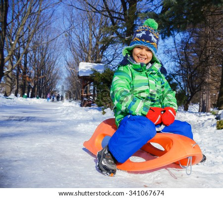 Little boy enjoying a sleigh ride. Toddler kid riding a sledge. Kid sled in snowy park. Outdoor winter fun for family Christmas vacation. - stock photo
