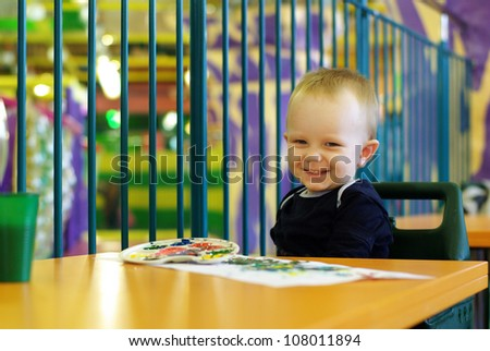 Little boy enjoying his painting - stock photo