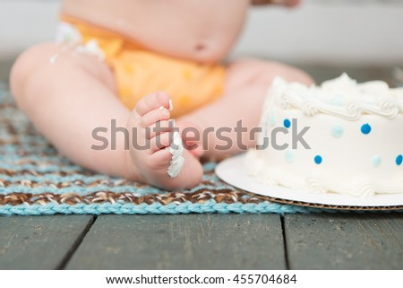 Little boy enjoys eating first birthday cake - stock photo