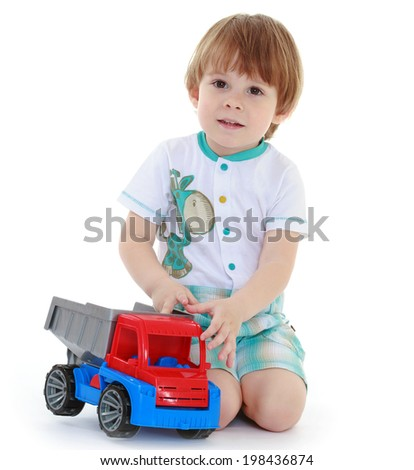 little boy enthusiastically playing toy car sitting on his lap. Isolated against white background - stock photo