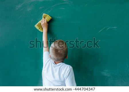 Little boy erasing chalkboard in the classroom