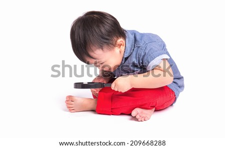 Little boy exploring with magnifying glass on white background - stock photo