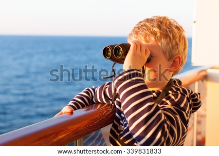 little boy feeling adventurous while cruising and using the binoculars