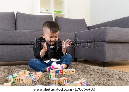 Little boy feeling excited to play toy block - stock photo