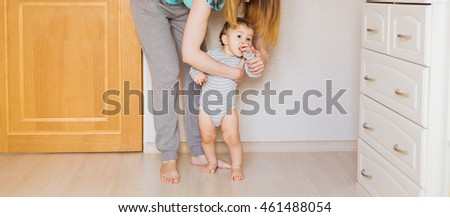 little boy first steps with the help of mother