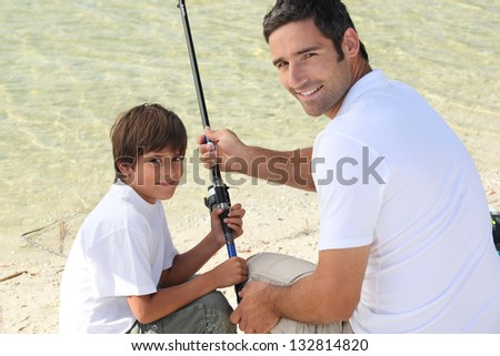 Little boy fishing with his dad - stock photo