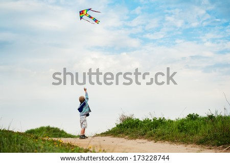 Little boy flies his bright kite into the blue sky, standing his back - stock photo