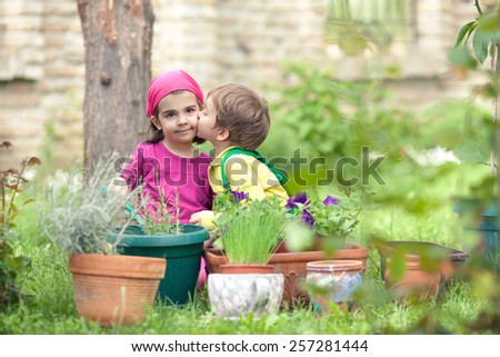 Little boy giving a kiss to his sister while playing in a garden - stock photo