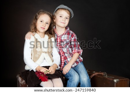 Little boy giving a red flower to a beautiful smiling little girl. Valentine day - stock photo