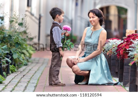 Little boy giving flower to his mom on mother's day - stock photo