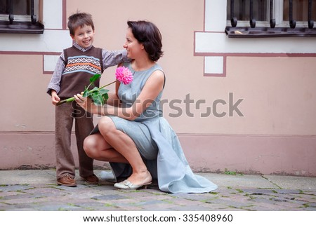 Little boy giving flower to his mom outdoors - stock photo
