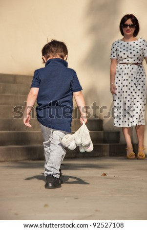 Little boy going with bowed head to Mom - stock photo