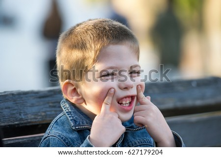 little boy grimacing while sitting on a bench