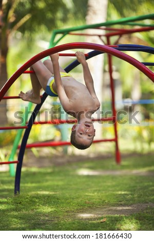 Little boy hanging on a monkey bars at the beach having a great time - stock photo