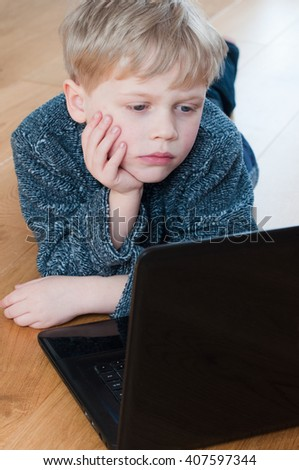 little boy hard at work using a laptop to do his homework - stock photo