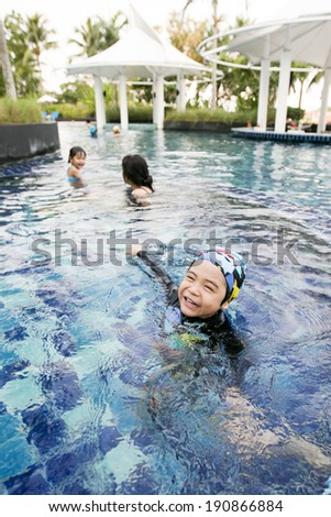 little boy has fun time with his family in the pool - stock photo
