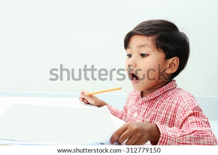 Little boy has surprising emotion with something in book on table. - stock photo