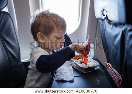 Little boy having a meal on board of a plane - stock photo