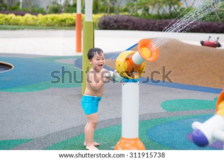 Little boy having fun at playground. Summer fun at the water park - stock photo