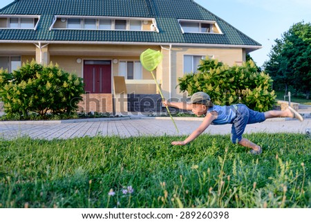Little boy having fun catching insects crouching down on the lush green lawn outside a house with a net in his hand