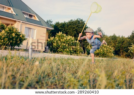 Little boy having fun catching insects crouching down on the lush green lawn outside a house with a net in his hand - stock photo