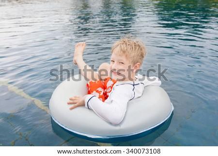 little boy having fun in the pool with inflatable ring - stock photo