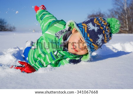 Little boy having fun in the snow - stock photo