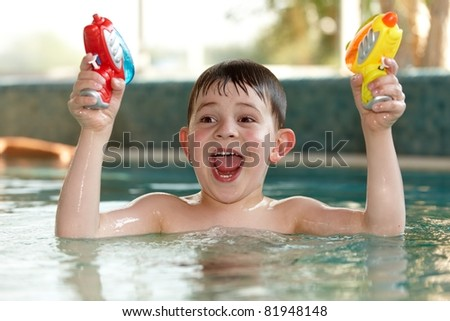 Little boy having fun with water pistols at swimming pool, laughing.? - stock photo