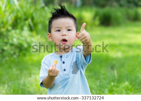 Little boy having his snack with thumb up gesture - stock photo