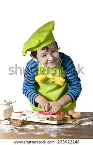 Little boy helps cook bake cookies for the holiday - stock photo