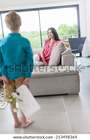 little boy hiding a gift for his mother in his back - stock photo