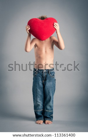 Little boy hiding himself behind a red heart. Valentines Day concept. - stock photo