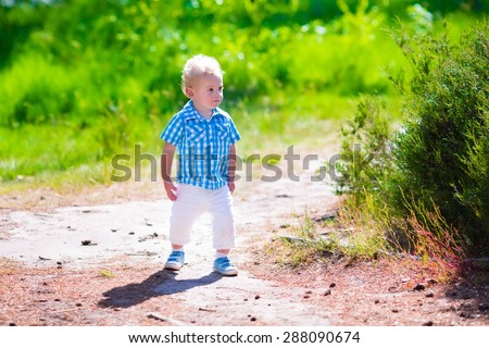 Little boy hiking in a forest. Outdoor fun for family in country side. Summer hike with young children. Toddler kid playing in a park. Child running in the woods. Kids play in wild nature. - stock photo