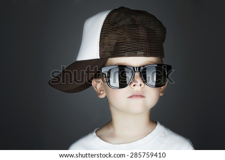 little boy.Hip-Hop Style. fashion children.handsome in sunglasses.in Tracker Hat. Young Rapper. Serious Child in Cap - stock photo