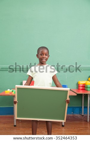 Little boy holding a balckboard