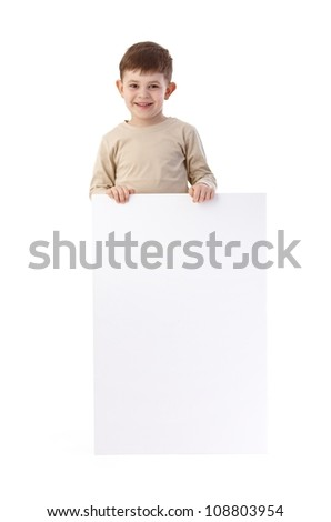 Little boy holding a blank sheet, smiling, looking at camera. - stock photo