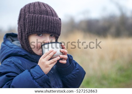 little boy holding a cup of tea outdoors. child drinks tea