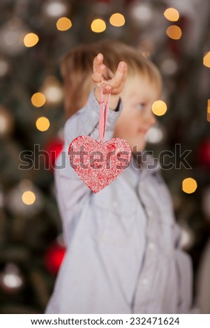 Little boy holding a red heart Christmas decoration standing in front of the lighted tree dangling it from his finger - stock photo