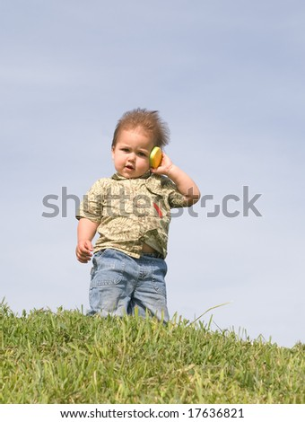 Little boy holding a toy cellphone near his ear - stock photo