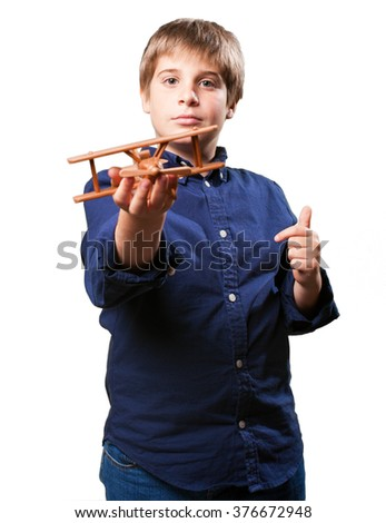 little boy holding a wooden biplane toy
